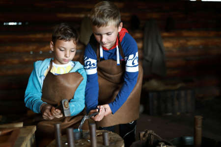 Two boys make coin in forge, Russia