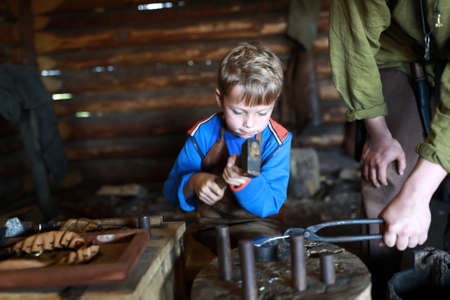 Child learning to work with hammer in forge
