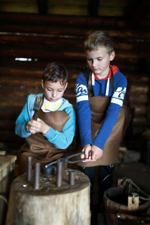 Two children make coin in forge, Russia
