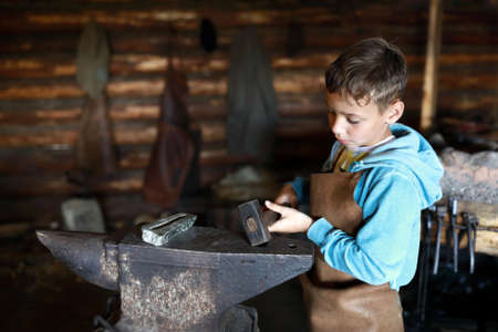 Kid hits anvil with hammer in forge Archivio Fotografico