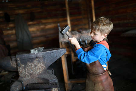 Child hits anvil with hammer in forge