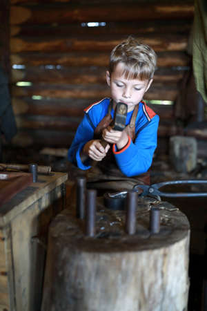 Boy learning to work with hammer in forge