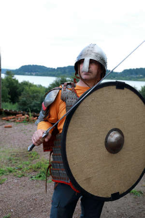 Viking posing in armor with shield and sword on shores of Lake Ladoga