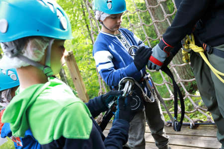 Instructor teaches children to use climbing equipment in park