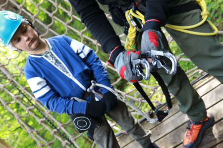 Instructor teaches child to use climbing equipment in park Zdjęcie Seryjne