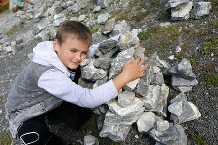Child putting stones in heap in marble canyon, Karelia 版權商用圖片