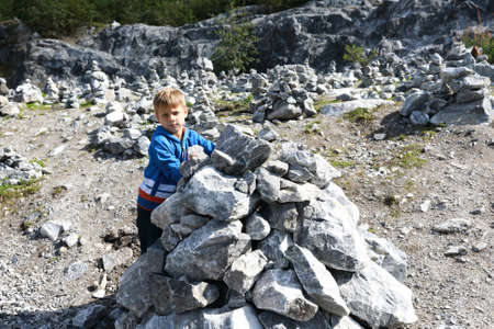 Kid puts stones in heap in marble canyon, Karelia