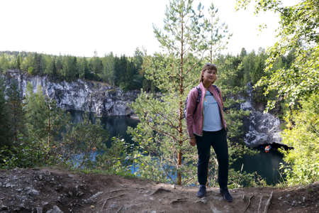 Woman on background of marble canyon, Karelia