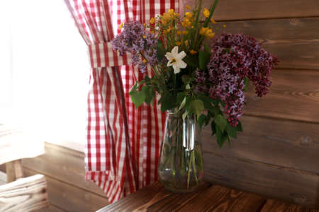 Carafe with wildflowers on wooden table at home