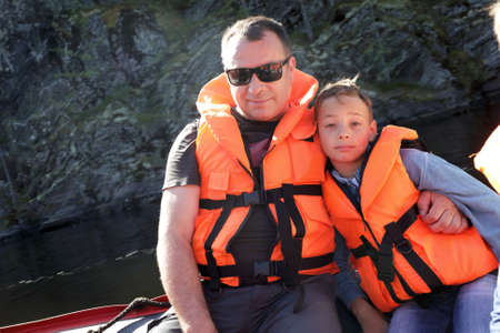 Father and son in life jacket on boat in Ladoga skerries