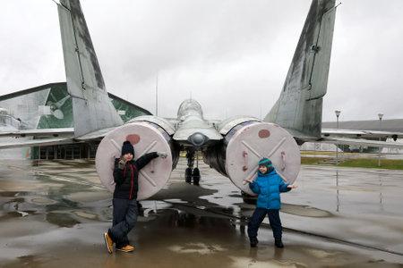 Children on background of Soviet multirole fighter Fulcrum, Russia Reklamní fotografie