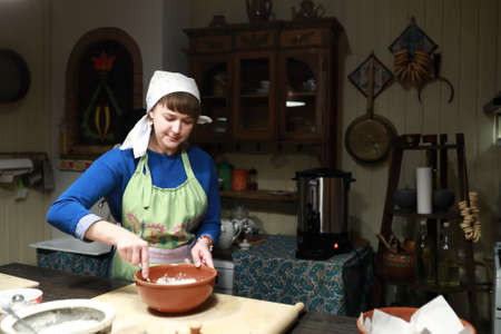 Woman making dough in bowl in kitchen