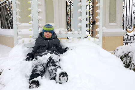 Boy sitting in snow on territory of Kazan Kremlin in winter
