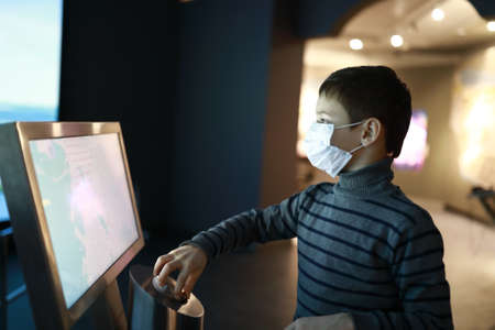 Kid in medical mask using touch screen in museum