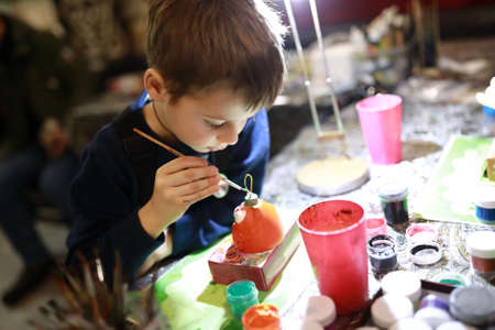 Boy painting a ceramic toy at workshop