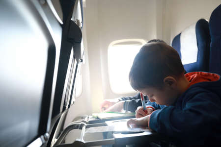 Child drawing on airplane during the flight Foto de archivo