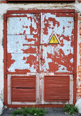 tacky: old red steel door on which the sign of danger