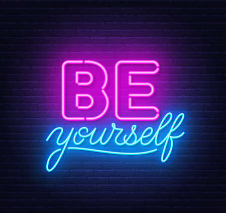 Be yourself neon inspirational quote on a brick wall.