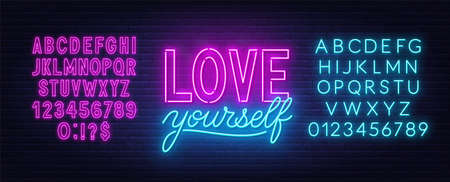 Love yourself neon inspirational quote on a brick wall.