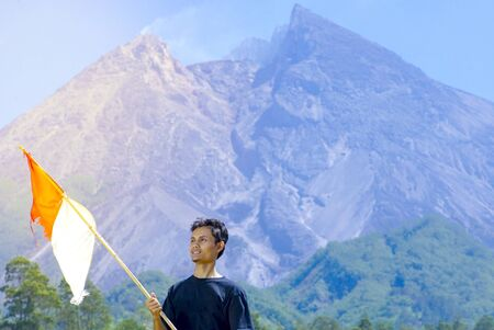 A man stand with Indonesia flag stands with Merapi Mt background. indonesia independence day celebration concept Stock Photo