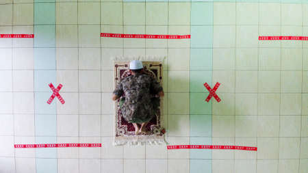 Indonesia April 17 2020 : Social distancing covid 19 young people praying in Mosque Indonesia, physical distancing in pray, Corona pandemi saat Sholat Indonesia, Pray at home 에디토리얼
