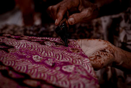 Batik, Close Up hand and canting, making Batik Tulis Indonesia. Canting is tool for drawing the texture on the fabric.