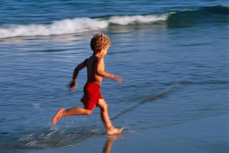 Boy in Swimwear, Running in Surf On Beach