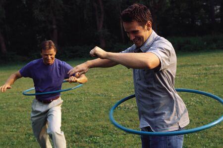 Men Using Hula Hoops Outdoors LANG_EVOIMAGES