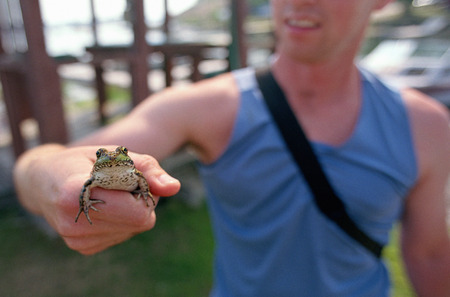 Close-Up of Man Holding Frog in Hand Outdoors LANG_EVOIMAGES