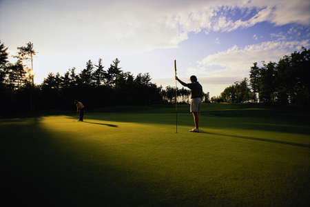 Golfer Putting on Green, Belgrade Lakes, Maine, USA LANG_EVOIMAGES