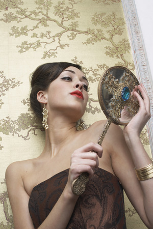 mirror image: Portrait of Woman Holding Mirror LANG_EVOIMAGES