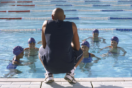 Coach and Students by Swimming Pool LANG_EVOIMAGES