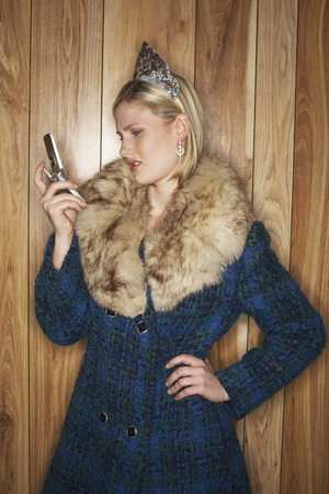 wood panelled: Woman with Coat and Crown Using Cellular Phone LANG_EVOIMAGES
