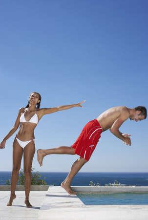Woman Pushing Man Into Swimming Pool LANG_EVOIMAGES
