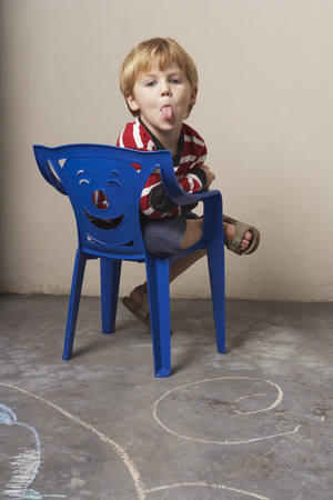 glower: Boy Sitting in Chair, Sticking Out Tongue LANG_EVOIMAGES