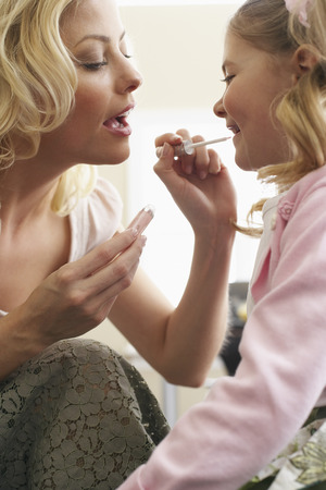 Mother Applying Lipgloss to Daughter