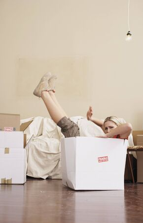 moving box: Woman Sitting in Cardboard Box