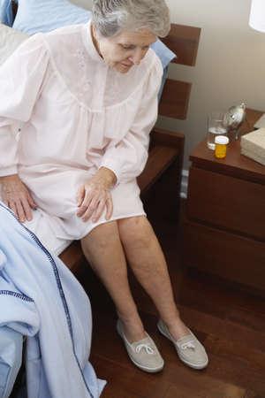 Elderly Woman Sitting on Bed LANG_EVOIMAGES