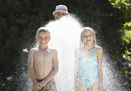 Children Being Sprayed With Garden Hose