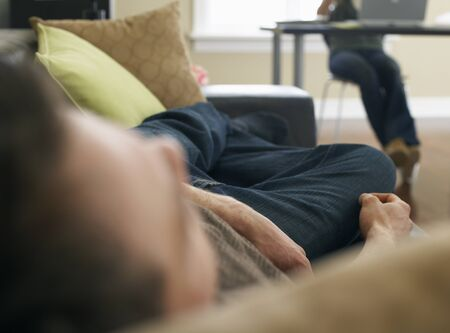 homeoffice: Woman Working at Computer and Man Napping on Couch