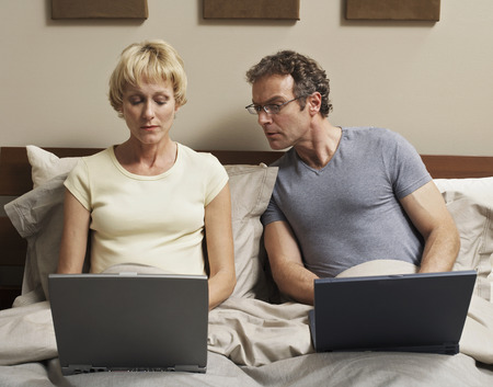 bedside: Couple Using Laptop Computers in Bed LANG_EVOIMAGES