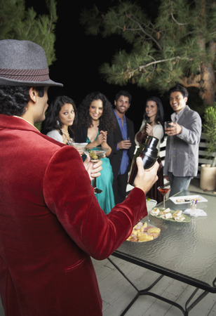 socialise: Man Holding Martini Shaker at Party LANG_EVOIMAGES