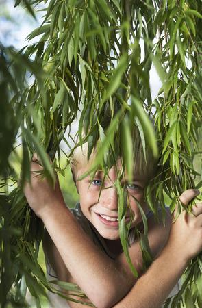 Boy Looking Through Foliage