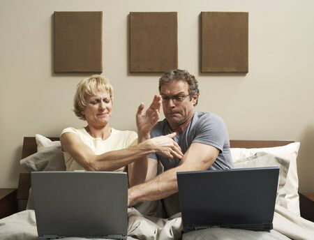 Couple with Laptops in Bed LANG_EVOIMAGES