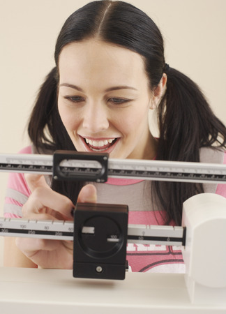women's issues: Woman Weighing Herself LANG_EVOIMAGES