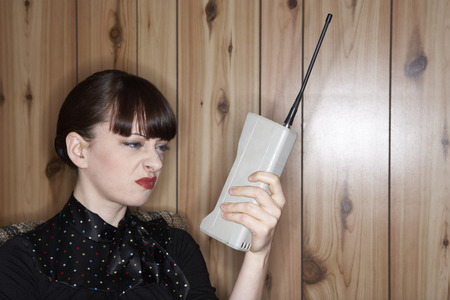 glower: Woman Looking at Old Cellular Phone