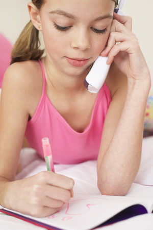 Girl Drawing in Notebook and Using Telephone