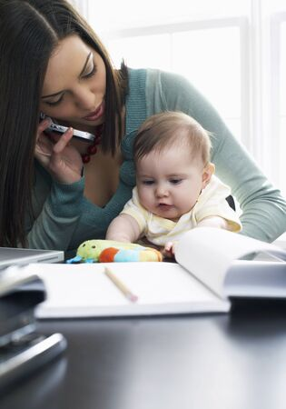 homeoffice: Mother Talking on Cellular Phone With Baby on Her Lap LANG_EVOIMAGES