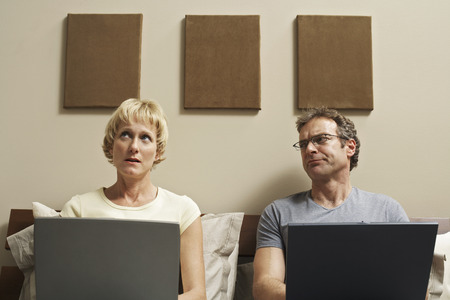 Couple Using Laptop Computers in Bed LANG_EVOIMAGES