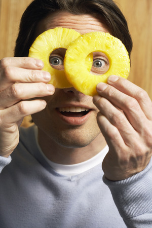 wood panelled: Man Looking Through Pineapple Slices